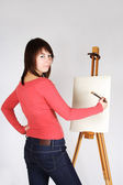 Young girl in red shirt standing near easel, painting and lookin — Stock Photo