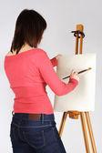 Giovane ragazza in piedi camicia rossa vicino a cavalletto e pittura, posteriore v — Foto Stock