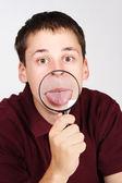 Büyüteç tutarak ve dil aracılığıyla gösterilen genç adam — Stok fotoğraf