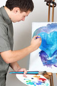 Closeup of man holding brushes and palette, painting blue abstra — Stock Photo
