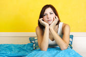 Young woman in white shirt sitting on bed, chin on hands, lookin — Stock Photo