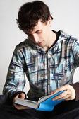 Young man in sport clothes sitting and reading book in blue cove — Stock Photo