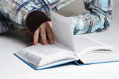 Closeup of man in sport shirt lying near opened book and turning — Stock Photo