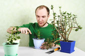 Man sitting near table with gardening equipment and pronging gro — Stok fotoğraf