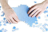 Closeup of mans hands assembling blue puzzle pieces, isolated — Stock Photo