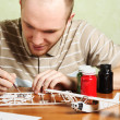 Man assembling plastic airplane model and painting pieces — Stock Photo #14762903