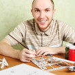 Man assembling plastic airplane model and painting pieces, smili - Stock Photo