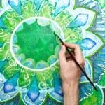Постер, плакат: Man painting bright green picture with circle pattern mandala o