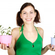 Young girl in green shirt holding potted plants and smiling, iso — Stock Photo