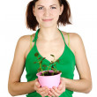 Young girl in green shirt holding potted plant and smiling, isol — Stock Photo