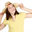 Young girl in yellow shirt and straw hat smiling and looking at — Stock Photo