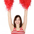 Beauty cheerleader girl in red shaking pompoms over her head, is — Stock Photo