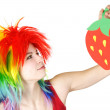 Young beauty woman in multicolored clown wig holding strawberry — Stock Photo