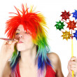 Stock Photo: Young beauty womin multicolored clown wig with party blower a