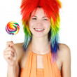 Young beauty woman in multicolored clown wig smiling and holding - Stock Photo