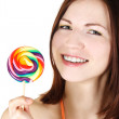 Young brunette girl holding big multicolored lollipop and smilin - Stock Photo