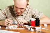 Man assembling plastic airplane model and painting pieces — Photo