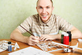 Man assembling plastic airplane model and painting pieces, smili — Stock Photo