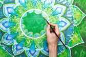 Man painting bright green picture with circle pattern, mandala o — Stock Photo