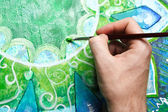 Closeup of man painting green picture with circle pattern, manda — Stock Photo