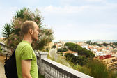 Young man on hill looking at European city — Stock Photo