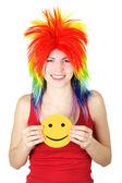 Mujer joven belleza en peluca payaso multicolor sonriendo y sosteniendo — Foto de Stock