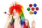 Young beauty woman in multicolored clown wig with party blower a — Stock Photo