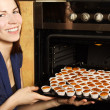 Young housewife taking cupcakes from oven and smiling — Stock Photo