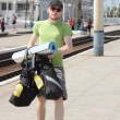 Bicycle tourist with backpack walking and railroad station — Stock Photo