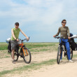 Two bicycle tourists standing on road, blue sky and horizon - Стоковая фотография
