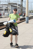 Bicycle tourist with backpack walking and railroad station — Foto de Stock
