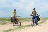 Dwóch turystów rowerowych stojących na drodze, błękitne niebo i horyzont — Zdjęcie stockowe