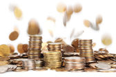 Stacks of silver and golden coins and falling coins on backgroun — Stock Photo