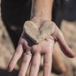 Sand heart in girls hand — Stock Photo #24452089