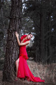 Attractive Model in Beautiful Red Dress next to Old Tree — Stock Photo