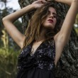 Sensual Young Model in Black Dress next to Tree — Stock Photo