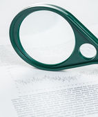 Magnifier on article — Stock Photo