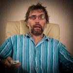Man looks terrible show on TV — Stock Photo #12716519