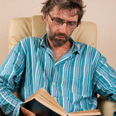 Man sitting in chair reading book — Stock Photo