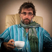 Sick man sitting in chair with cup — Stock Photo