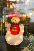 Snowman in holiday window — Stock Photo