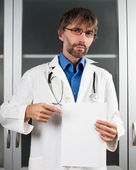 Doctor shows blank sheet of paper — Stock Photo