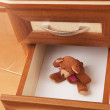 Teddy bear in open desk drawer — Stock Photo