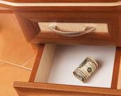 Roll of dollars in open desk drawer — Stock Photo