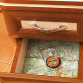 Map and compass in open desk drawer — Stock Photo