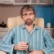 Drunk man sitting in chair with glass — Stock Photo #18434809