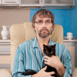 Man sitting in chair with kitten — Stock Photo #18627231