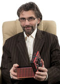 Businessman sitting in chair with gift — Stock Photo