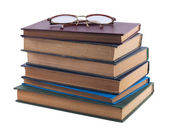 Pile of old books and vintage glasses — Stock Photo