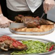 Stock Photo: Cook cut up roast lamb leg